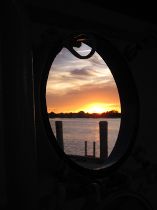 The porthole view of a sunset approach to Block Island, from the vehicle deck of the Pt. Judith ferry.